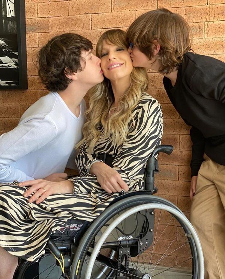 Foto de uma mulher sentada na cadeira de rodas, usando um vestido sendo beijada nas bochechas por seus dois filhos, um a sua direita, e um a sua esquerda. Ela sorri,