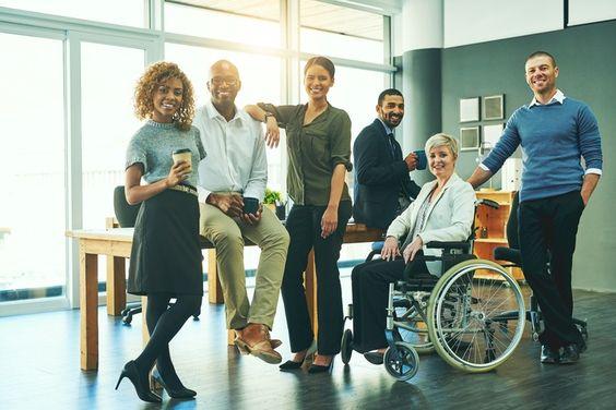 Grupo de pessoas em uma empresa, da esquerda para a direita, mulher negra, segurando um copo de café, homem negro sentado em uma mesa, segurando uma xícara, mulher negra com o braço apoiado no homem ao seu lado, homem negro sentado no final da mesa, uma mulher branca em uma cadeira de todas, um homem branco atrás dela. Todos sorrindo.