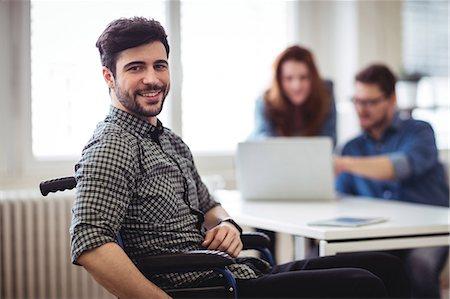 Homem sorrindo na cadeira de rodas, ao fundo, uma mulher e um homem usado um notebook. Foco da imagem na diversidade