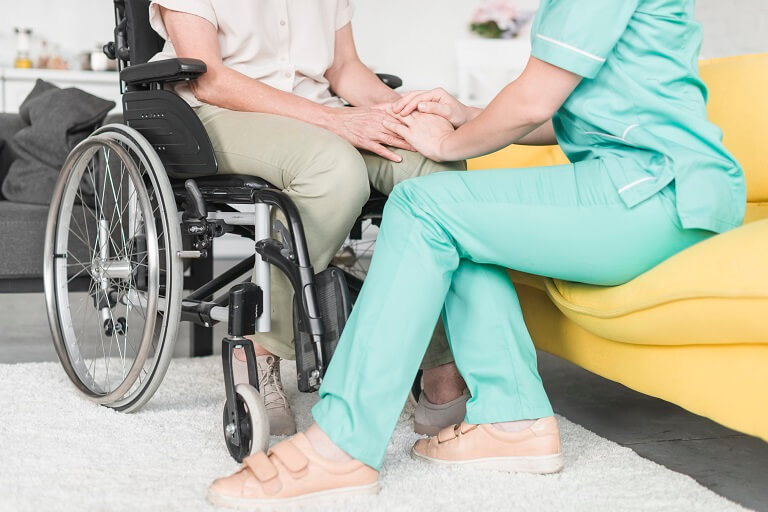 Na foto, uma pessoa com deficiência sentada na cadeira de rodas, ao lado de uma cuidadora. Essas pessoas deveriam ser incluídas no grupo de risco da COVID-19.