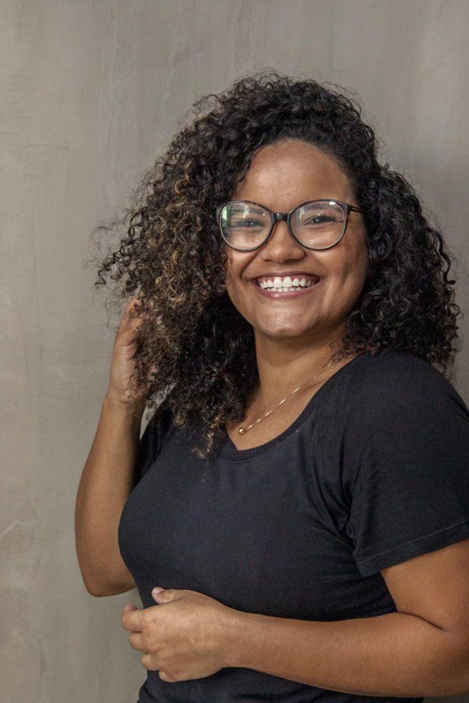 Na foto, Laura Barbosa, mulher negra, sorrindo, com a mão direita no cabelo cacheado. Posou para ilustrar a matéria sobre diversidade.