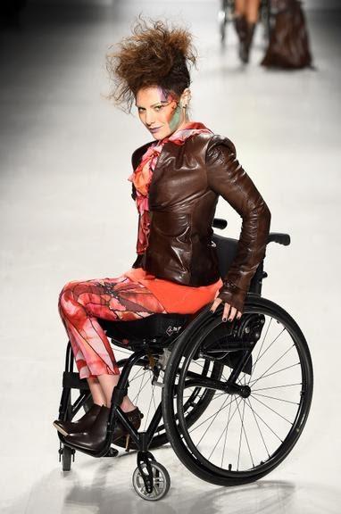 Modelo vestindo jaqueta de couro, legging e bota, sentada em uma cadeira de rodas, desfilando na New York Fahsion Week, por mais representatividade.
