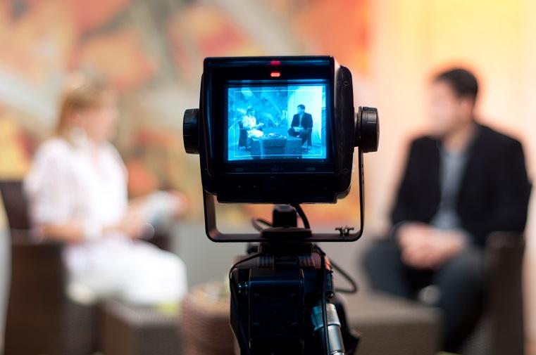 Imagem de palestras online, há uma câmera no centro da imagem focando em uma mulher vestida de branco, e um homem com terno preto e camisa azul