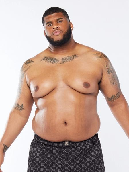 Modelo da fenty, um homem negro, gordo, com estrias na barriga, tatuagem no colo e nos braços, de barba e usando uma cueca da grife.