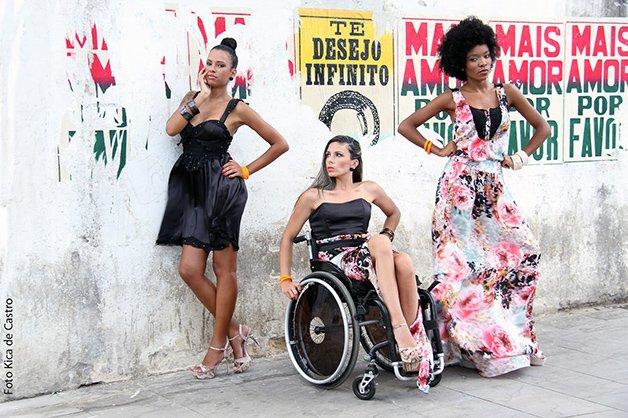 Na imagem, tres modelos aparecem posando com roupas diferentes, uma negra com vestido preto, uma cadeirante de rodas com blusa preta e saia florida e outra mulher negra com vestido florido. Práticas que tornam o mercado mais inclusivo