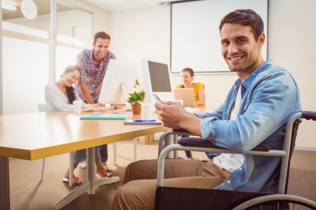 um homem branco, cadeirante de rodas, de cabelos castanhos sorrindo enquanto segura um celular. Atrás dele duas mulheres e um homem trabalhando em computadores. Imagem utilizada para dia mundial das pessoas com deficiência.